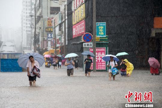 """台风""""电母""""给海口带来暴雨天气,市民涉水出行。 洪坚鹏 摄"""