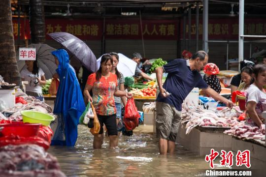 海口城市内涝,市民在积水的农贸市场采购。 洪坚鹏 摄