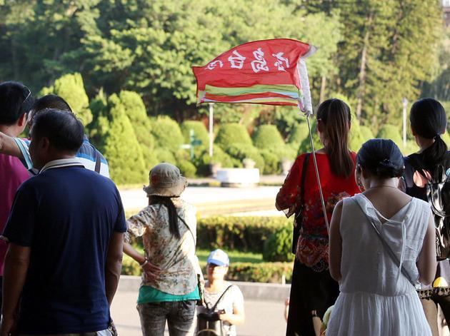 """陆客赴台人数锐减,对旅游业界造成冲击,导游手持的""""宝岛台湾""""旗帜。(图片来源:台湾联合新闻网)"""