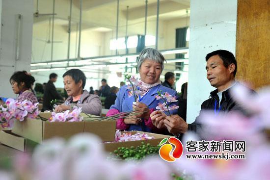 贫苦户就近在龙南县失业扶贫福利厂任务。图为工人在手工制造装潢品。