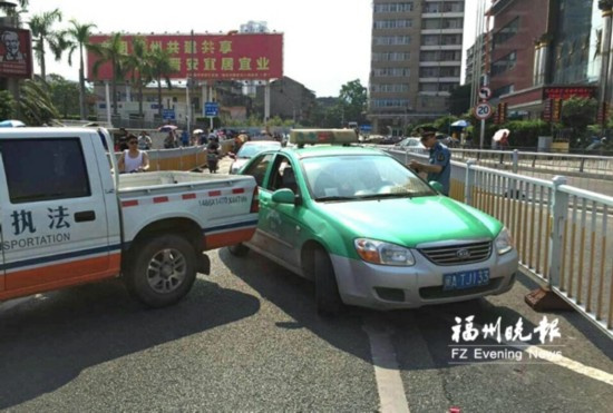 执法人员拦截被投诉出租车。