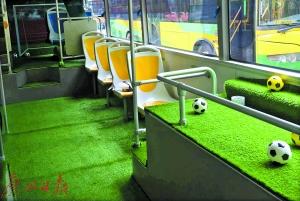 """双层巴士车箱内到处可见足球元素,特别是有""""高仿真绿草地""""的地板和足球乐土模子区。广州日报记者乔军伟 通信员华成锋 摄"""