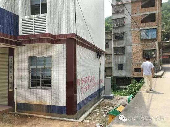 一位村民从魁斗乡司法所旁经过,司法所墙壁上有打击电信诈骗的标语。新京报记者 谷岳飞 摄