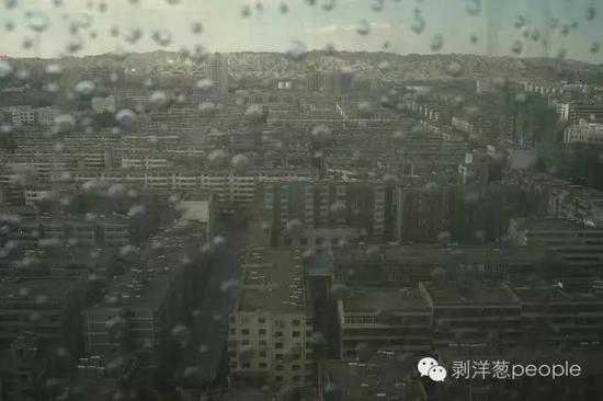 8月31日,从白银市中心的制高点鸟瞰,灰色的楼群连接着远处灰色的群山。