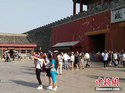 游客在故宫北门外用自拍杆合影。中新网记者 宋宇晟 摄