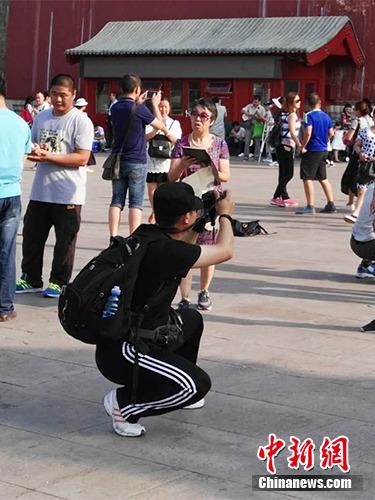 游客在故宫北门外拍照。中新网记者 宋宇晟 摄