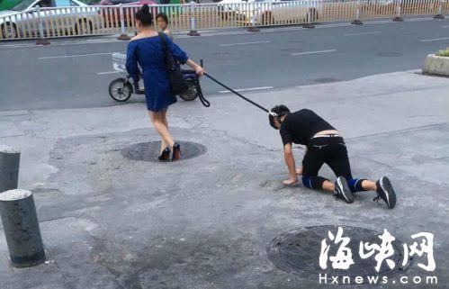小伙脖子拴绳被女子牵着当街爬行