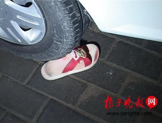 女孩所穿一只拖鞋散落在小区地面。