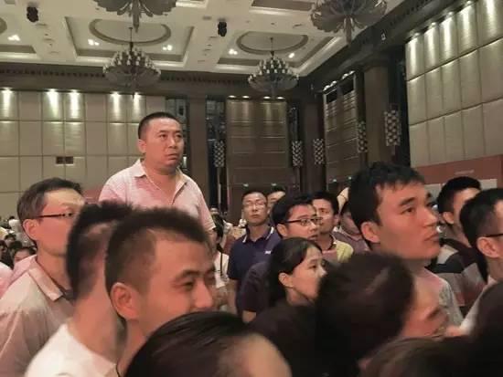 9月10日,郑州,某楼盘进行摇号售房,一位购房者站在椅子上在大屏幕上寻找自己的号码。 周波/视觉中国 摄