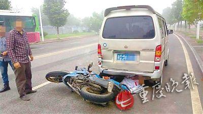 摩托车驾驶员卡在面包车下