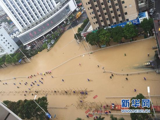 """福州火车站南广场前""""沦陷""""。一早,工作人员到现场搭建临时桥,供行人出行。(图/新华网)"""