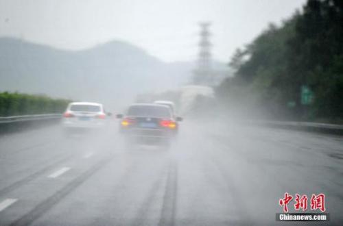 """9月27日,强台风""""鲇鱼""""给福建莆田带来了强降雨,车辆纷纷减速行驶。中新社记者 张斌 摄"""
