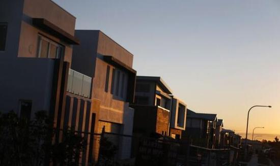 资料图片:夕阳映照着正在修建中的悉尼百万美元住宅区。