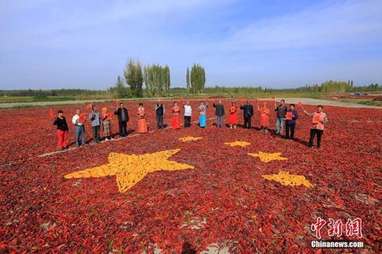 9月29日,新疆博湖县才坎诺尔乡农牧民团聚在一起,用辣椒、玉米等拼成一副别样壮美的五星红旗,喜迎祖国67周年华诞。来源:中新网