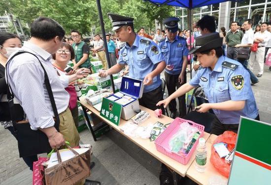 """2015年6月7日,南京市第九中学考点门前的""""城管护考""""服务点,城管队员向考生免费赠送考试文具、药品等物品"""