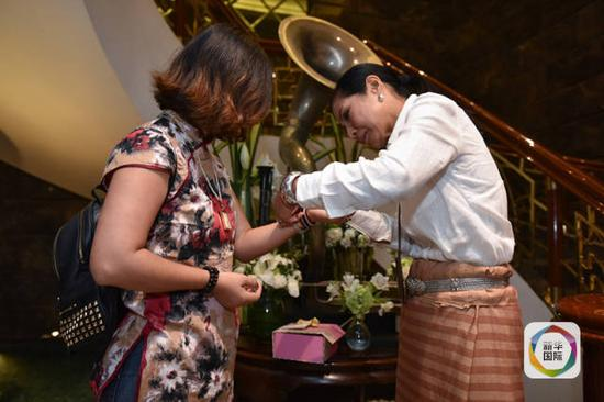科甘(右)为杨莉佩戴象征泰国国旗三色的手链。(新华社记者李芒茫摄)