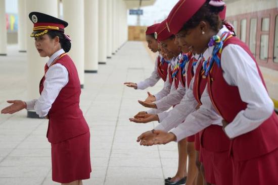 中方列车长丁继华(左)指导埃塞俄比亚乘务员练习迎宾礼仪。