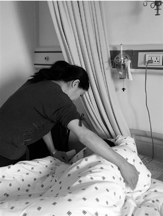 汪华君关照病床上的儿子。詹程开 摄