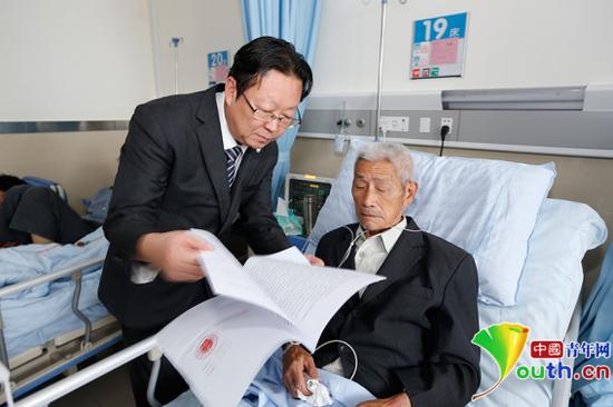 9月29日,邱少云名誉权案代理律师向病床上的邱少华老人传达判决书内容。那一天,老人特意嘱咐家人为其换上了正装。中国青年网记者 张炎良 摄