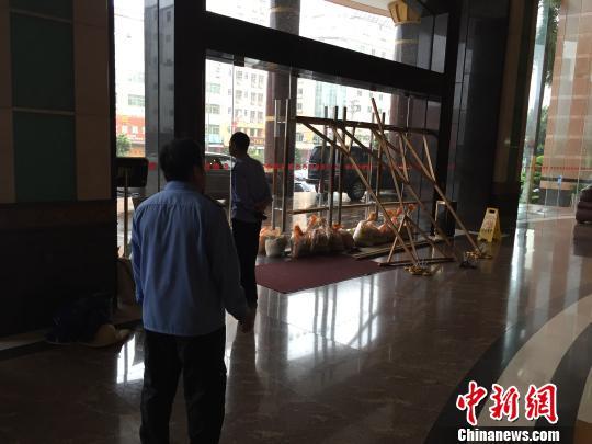 汕尾海丰一酒店工作人员正用沙袋、木头搭起支架抵住大门,防御台风。 陈启任 摄