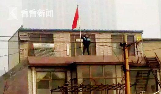 网上流传的贾敬龙家被拆时照片,贾敬龙举着红旗站在楼上
