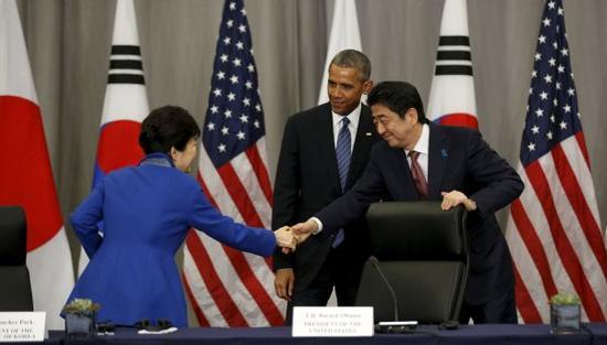 2016年3月31日,在美国首都华盛顿,韩国总统朴槿惠(左)和日本首相安倍晋三(右)在美国总统奥巴马(中)的注视下握手(资料图)