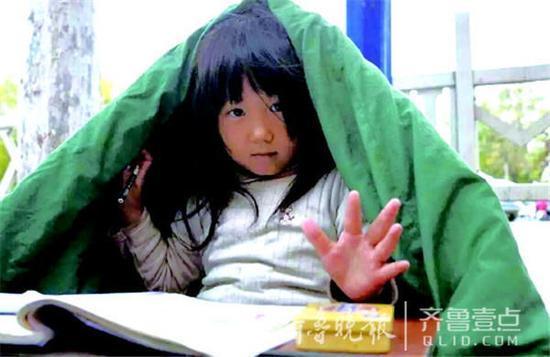 10月23日,季红红在临沂街头披着棉被写作业。据沂蒙晚报