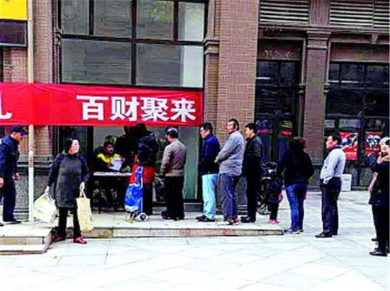 领白菜的业主排起了长队。 记者 王僖 摄