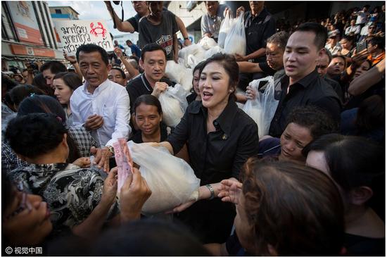11日,泰国曼谷街头,英拉帮米农卖大米。
