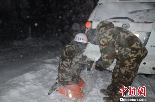 图为消防救援人员给被困车辆安装救援绳。 李江江 摄