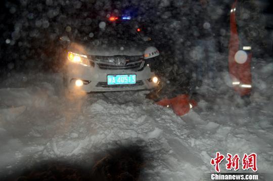图为消防人员跪在雪地里用铁锹铲雪救援被困车辆。 李江江 摄