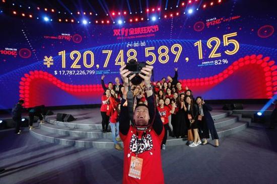 """11月12日,工作人员在广东深圳举行的活动上庆祝天猫""""双十一""""全天成交额超过1207亿元。 新华社记者沈伯韩摄"""