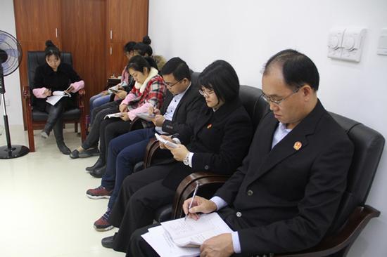 图为法官们认真做学习笔记。