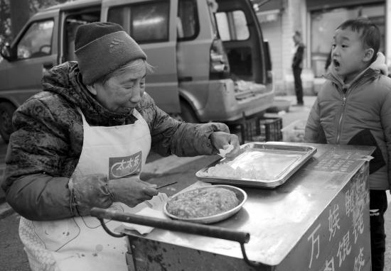 11月27日,长沙蒋家垅社区,小朋友向正在包馄饨的万��泊蛘泻簟M�/记者陈韵骄