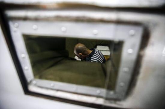在梅州监狱的禁闭室里,方某戴着脚镣和手铐,一脸茫然。 金羊网 图