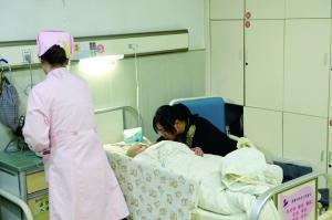 护士在为晓恬换药,妈妈在一旁照顾她 现代快报/ZAKER南京见习记者 吉星 摄