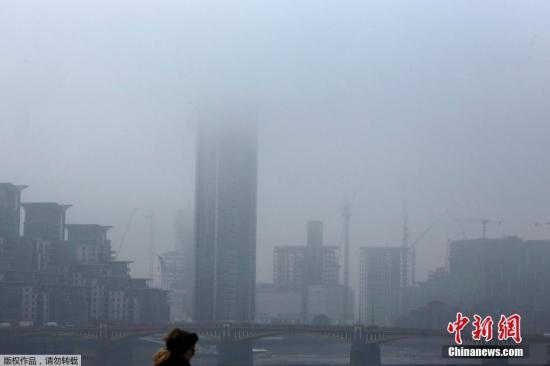 当地时间2016年10月31日,英国伦敦早上出现大雾天气。图为市民在雾中行走。