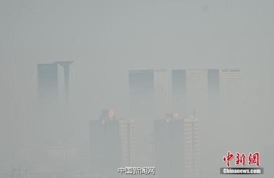 图为石家庄街头,在建楼盘被雾霾笼罩。 中新社记者 翟羽佳 摄