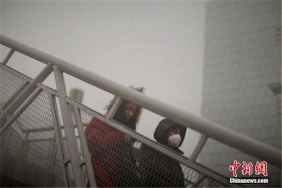 ↑12月4日,戴着口罩的行人从天桥上走过。天津市气象台当日7时发布大雾橙色预警信号,天津大部分地区笼罩在大雾中,局部地区能见度低于200米。