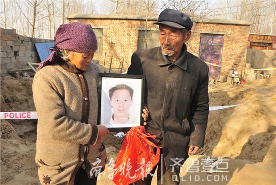 老两口抱着儿子的遗像,悲痛不已。齐鲁晚报・齐鲁壹点 记者 邹俊美 张蔚 摄