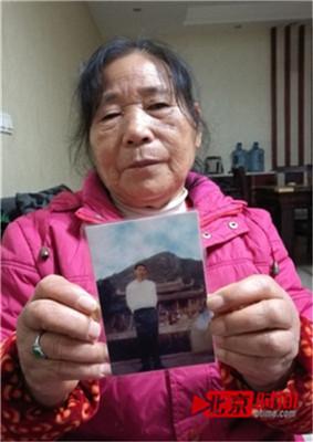 包玉贞拿着丈夫范安银的遗照。图/北京时间