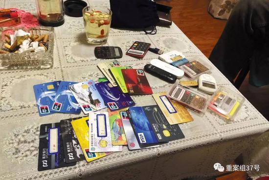 11月28日晚,燕郊东方夏威夷南岸二期10号楼501室,一名C1家长(传销头目)向刘奇等人展示自己的18 张银行卡和信用卡。新京报记者大路摄