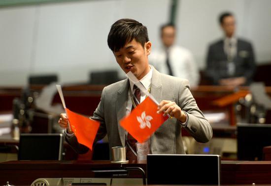 郑松泰早前倒插建制派议员��上的国旗、区旗,引起社会各界强烈不满/资料图片