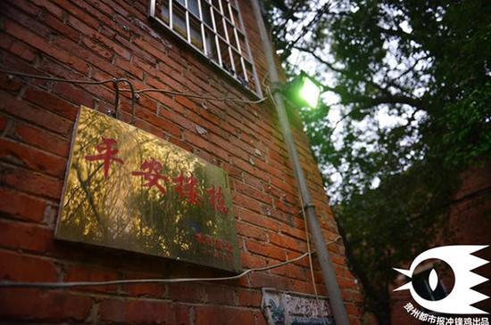 """2015年9月,宿舍楼墙壁上挂着""""平安楼栋""""牌匾。"""