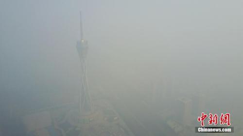 12月18日,河南郑州仍是雾霾围城,图为隐身于雾霾之中的河南广播电视发射塔。王中举 摄