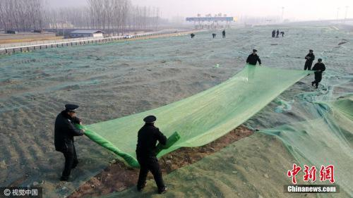 12月16日,北京大兴区城管队员正在苫盖建筑垃圾。图片来源:视觉中国
