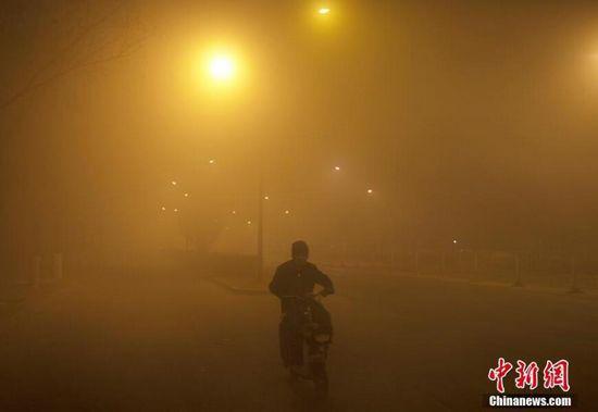 12月18日,北京市民在雾霾中出行,能见度极低。中新社记者 刘关关 摄