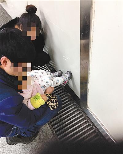 一对年轻父母在公厕门口给孩子把尿