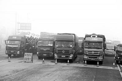 等待高速通行的大车排起了长队。