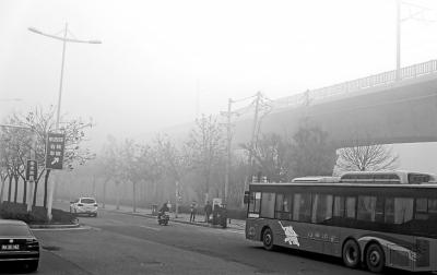 大雾中,不少人在等车。